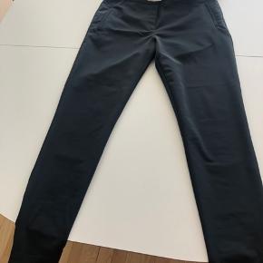 Koks grå bukser med lynlås i siden og nederst på benene. Bukserne kan bruges til hverdag og fest.