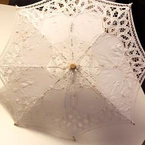 Paraply i stof, en pind er knækket men er stadig funktionel.