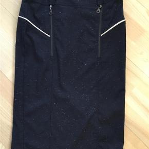 Varetype: Nederdel Farve: Mørkeblå med nister  Mørkeblå pencil nederdel med lynlås bagpå og gålæg sælges. Længde medi. Hvidt pyntebånd som på foto.  Længde 70 cm. Livvidde 78 cm. Hofteviddede 98 cm.