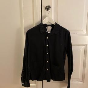Skjorten er både til mænd og kvinder. Mand str. 48 og kvinde str. 38. Den har små smarte lommer foran.