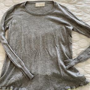 Bemærk den fine detalje med at blusen går længere ned foran end bagved.  45% uld, 35%nylon, 20% silke- blød og lækker. Vasket på uldprogram