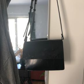 Ganni crossbody taske. Er brugt en del så har tydeligt slid. Knappen er faldet af men tasken kan dog stadig lukkes. Skriv endelig hvis du har brug for flere billeder 🖤 Byd gerne ✨