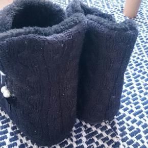 Sutskostøvler / sutsko i sort kabelstrik med glimmer nistrer i stoffet, og med detaljer på siderne med skinnende sløjfer og perler samt skridsikre dupper under. Prøvet på, men aldrig brugt.