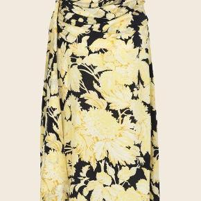 Stine Goya Nederdel - Lilly skirt, Hortensia Dark  Luksuriøs silkenederdel fra Stine Goya med smukt lysegult blomsterprint på sort bund. Lilly Skirt har elastik i livet, lynlås i siden og et bredt bindebælte som bindes i siden. Nederdelen har et let svaj som og giver den et feminint look.  Brug den smukke nederdel til sæsonens fineste begivenheder tilsat høje hæle og en smuk top eller når hverdagen skal være ekstra eller sneakers og en cool statement t-shirt.  100% silke renses kryber max 3-5 %
