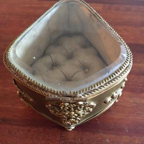 Sælger dette super smukke messing skrin med glas låg, og silkepude indvendig. Det er nok fra omkring slutningen af 1800 tallet. Men alderen taget i betragtning er det i god stand. Det har en lille rids i glasset og et af benene er lidt skævt.  Det er 13 cm i længden og 8 cm i højden.   Giv et realistisk bud.   Skal afhentes i lystrup eller sendes mod betaling.
