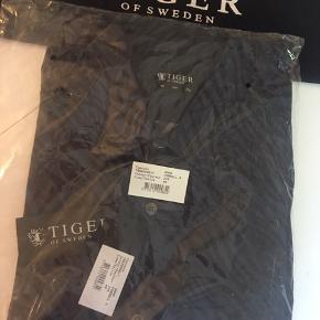 Farrell Shirt  Shirt in cotton Slim fit Shaped hem with triangle patch detail at sides Made in Europe Colour Light Marine/Black 2V5  Aldrig brugt Kan sendes med DAO Nypris 1095 kr.  Pris er fast og eksl. transport