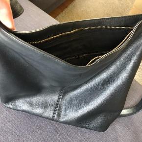 Smuk taske i ægte læder i enkelt og stilrent design fra Markberg.  Tasken er kun brugt i en kortere periode og fremstår næsten som ny. Der er ikke meget slitage på tasken, den smule der er, er forsøgt vist på de sidste to billeder.  Remmen er lang, og kan indstilles, så man kan bære den crossbody eller som skuldertaske. Den er rummelig og godt indrettet. To lommer og et lukket rum. Tasken lukkes med lynlås.  Mål kommer snarest.  Np. 1499,-   575,- + fragt.  Fragt betales af køber. Jeg sender gerne med Dao eller gls.  Bytter ikke.