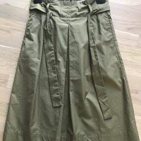 Fin nederdel til under knæ. A-facon med fast talje og bindebælte. Lynes bagpå.