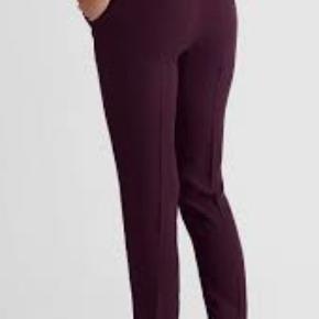 """Helt nye flotte velsiddende bukser med pressefold foran og bagpå. Smidig """"træk på-model"""" med elastik i taljen bagpå samt lommer i siderne. Fremstillet i vævet kvalitet. Benlængde ca. 70-72 cm.   Bordeaux farvet, str. 40. ALDRIG BRUGT. Talje:Normal talje, 100% Polyester."""