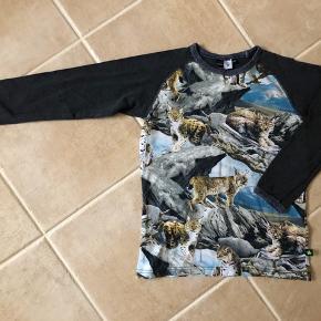 """Super lækker bluse fra skønne Molo, str. 140. Blusen har print med flotte geparder af en slags, foran og bagpå, og mørkegrå ærmer. Ingen huller eller pletter naturligvis. Standen er lidt under """"næsten som ny"""". Er kun blevet vasket på 30 grader med Woollite, som holder på form og farve. Den er sååååå fin ☺️   Se også mine andre annoncer. Se om der er mere der frister 😊 Jeg har rigtig meget drengetøj i den størrelse 👍🏻🙈"""