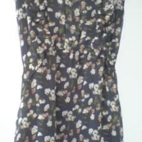 Brand: Roshi Varetype: grå mønstret blomstret tunika top flæser ved bryst Størrelse: M/L Farve: Grå  Tunika/top i mørk grålig med blomster, lukkes med lynlås i siden.  65 % chiffon 35% polyester  bryst ca. 2 x 47 cm. længde ca. 80 cm.   Porto er sendt som forsikret pakke med Dao, med mindre andet aftales.