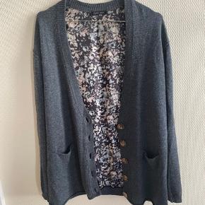 Lækker cardigan fra Stella Nova med mønstret ryg og glimmerdetaljer på albuerne. Cardiganen har desuden små lommer foran.    50% uld og 50% bomuld.