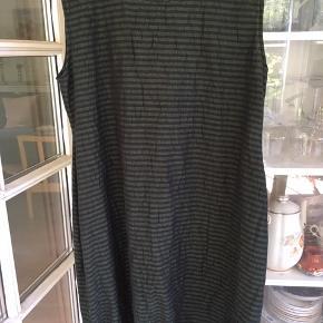 Mørkegrøn/sortblå smalstribet kjole fra Masai i fitted facon. Materialet er 66% bomuld, 34% polyester. Kjolen afsluttes med elastikkant forneden.  Mål: Brystmål fra ærmegab til ærmegab: 2 x 58 cm Talje: 2 x 54 Hofte ca. 2 x 64 cm Længde: 100 cm Jeg sender med Dao til nærmeste pakkeshop.