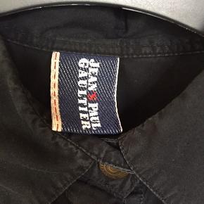 Så fed vintage JPG skjorte, købt tilbage i 90'erne og ikke brugt særlig meget, men man kan self se, at den har været vasket nogle gange - som altid med sorte skjorter i bomuld. Lilla pipings gør den en smule westernagtig. Byd på dette unikum😉