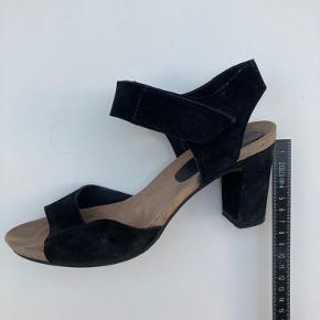 Dejlig heels fra Billi Bi i sort ruskind. Hælen er 7 cm og skoen lukkes med en velkrorem, så den kan justeres i størrelsen om anklen. Bunden er en slags kork, som giver en fin effekt i siden.