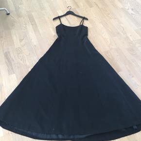Smuk sort gallakjole. Sort let skinnende stof. Smuk ryg.  Et enkelt lag tyl i skørt så kjolen falder flot.
