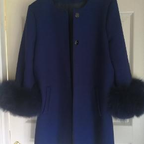 Smuk blå jakke med aftagelig pels på ærmerne. Modellen hedder Golla.  Str hedder L/XL. Den er lille i størrelsen og passer en str 38/40. Brugt 2 gange.