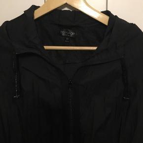 Varetype: Jakke Farve: Sort Oprindelig købspris: 399 kr.  Topshop jakke. Sort. Str. 42. Lynlås. Hætte. Elastik og bindebånd forneden. Længde ca. 53 cm, bredde ca. 51 cm. 100 % nylon.