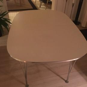 Fint spisebord med hvid overflade og metalben. I rigtig fin stand.Kan afhentes i 5450 Otterup.  Højde: 71 Bredde: 102 Længde: 150