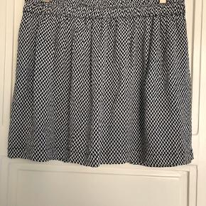 Fin nederdel i hvid/mørkeblå med elastik i taljen og underskørt. 100% viskose.  Bytter ikke!