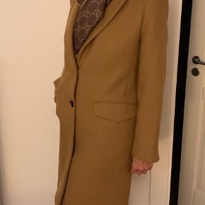 Lækker frakke i uld med knapper . Kun brugt få gange.  Materialet er : 75% uld/ 25% polyamid