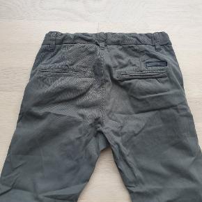 Kun brugt en smule og ingen slid at se. Der er skrevet navn inde i bukserne. Pæn mat, vissengrøn farve.