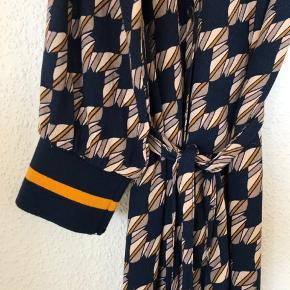 Smuk lang skjortekjole i 100% viscose med grafisk mønster i mørkeblå, sand og brændt orange. Ærmer i rib. Har bindebælte. Kan knappes op og bindes så ryggen og dermed bruges som kimono.