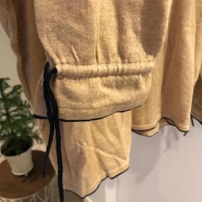 Varetype: Rullekrave Farve: Beige Oprindelig købspris: 1099 kr.  Ubrugt højhalset bluse sælges. Sød bindebåndseffekt ved ærmerne.
