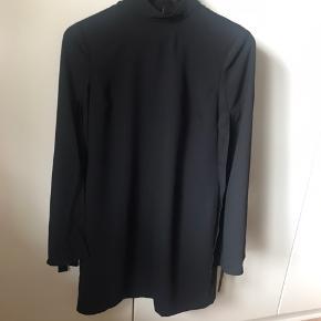 Sort kjole fra Day. Længde 92 cm, Brystmål 90 cm. Sjov detalje på ærmer, som ikke er syet sammen hele vejen, men bliver lukket med et bånd. Virkelig fin kjole som kun sælges, da jeg ikke kan passe den.