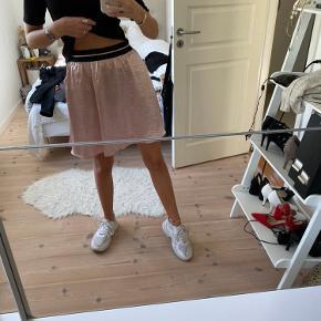 Sød lyserød nederdel med lommer og sort bånd i taljen