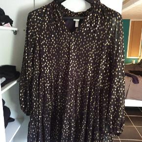 Sød lille midi kjole i sort og guld.. bruges med leggins eller bukser.  Brugt 2 gange