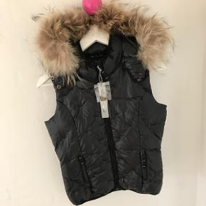 Lækker, ny Ver De Terre vest med den flotteste vaskebjørns pels sælges. Har elastik indvendigt til at stramme ind forneden. Nypris 1199 - BYD 😊 Er en størrelse 12 år.