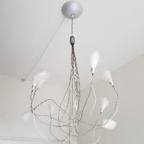 Moderne lysekrone med 9 pære (60 W). Lampeskærmerne i plast kan foldes efter eget design og ærmerne i blødt metal kan drejes både op- og ned og til siderne som man ønsker. Købt i butik i København for 3.800 kr.