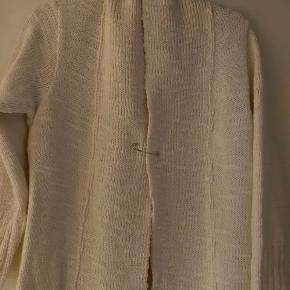 Smuk og lækker lang strik cardigan i creme hvid. Cardiganen har ikke knapper, men lukkes istedet med en XL - sikkerhedsnål, der gør cardiganen lidt ekstraordinær. Man kan også vælge at lade den stå åben. Er lavet af 50% Uld og 50% Acryl. Længde ca. 102 cm. og brystmål ca. 53 cm. målt fra ærmegab til ærmegab.