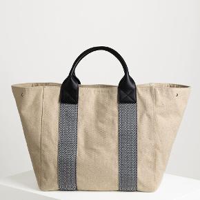Denne store casual taske er nem at bruge og altid elegant, og så er den perfekt til weekendrejsen eller til en hyggelig dag på stranden. Den har et stort rum og en lille indvendig lomme med lynlås, så der er plads til alt, hvad du har brug for. Stoffets naturlige farve, som står i kontrast til læderstropperne og de vævede striber, er med til at skabe et blødt og minimalistisk look. Korte læderhåndtag Siderne kan knappes op for ekstra plads 73 x 37 x 21cm 55% hør, 45% bomuld  Nypris 2199.- Kvittering haves.  Bytter ikke og prisen er fast.