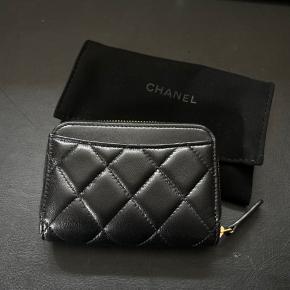 Jeg sælger denne lækre Chanel zipped coin purse da jeg aldrig har brugt den og rydder ud af jeg flytter til London.   Alt medfølger, inklusiv kvittering, dustbag og autencitetskortet.   Købt i butikken i København i maj måned 2020.   Min taske er for lille til den og det fungerer fint med en kortholder for mig.   Ved spørgsmål eller ønskes flere billeder, skriv endelig. Kan ikke sætte flere billeder på annoncen.