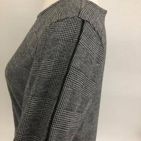 Flot kjole med sorte og råhvide tern fra VRS med lange ærmer.  Tynd sort stribe påsyet langs oversiden af begge ærmer. Lukkes med lynlås i ryggen.  Længde fra skulder er 97 cm, brystmålet er 106 cm, og taljen måler 102 cm.  Fremstillet i dejlig lun kvalitet af 65% polyester, 31% viscose og 4% elastan.  Bærer ikke præg af brug.