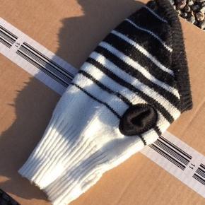 Har en sort/hvid hunde strik trøje  Måler ryglængde 26 cm (fra rib ved halsen) og brystmål ca 34 cm. Total længde med rib 36 cm