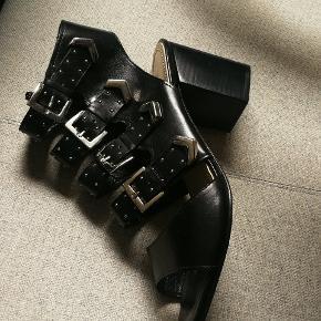 Blokhæl sandal med mini studs % metal detaljer. 4 remme. Lynlås på indersiden. Lædersål med gummi-insert.