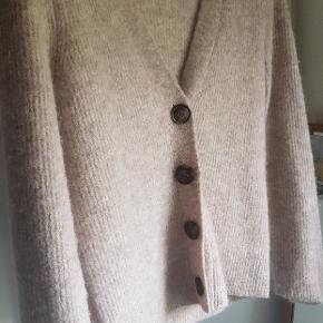 Skøn beige cardigan i en lækker rib strik fra Neo Noir. Cardiganen har en dyb v-udskæring med knapper hele vejen ned, normal pasform med smalle ærmer.  32% alpaca 32% merino uld  30% polyamid  6% elastan