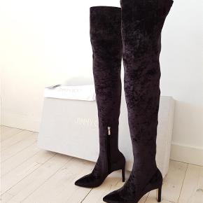 Varetype: støvler Farve: Sort  Sælger mine helt nye, vildt smukke, sorte Jimmy Choo over-the-knee støvler. Hælen er 8,5 cm så de er utrolig behagelige at have på. Købt 2018 I Illum for 9300 kr. Jeg har aldrig brugt dem (kun lige prøvet på hjemme) og de fejler absolut intet. De er stretchy så sidder godt og falder ikke ned. Str 36 og normale til lidt store I størrelsen. Mp 5000 kr.  Obs: Lyset driller lidt men de er altså helt sorte