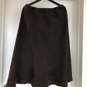 A formet nederdel i polyester  Mål:  Ø: 76 L: 81