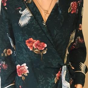 Slå-om bluse/skjorte med bindebånd. Mørkegrøn med blomster og storke.