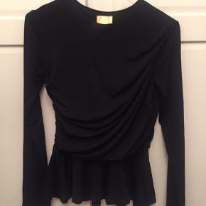 Fin bluse fra H&M i str. 36. Draperinger foran, lange ærmer og peplum effekt nedadtil. Tætsiddende.  Kan sende med DAO, køber betaler fragt.
