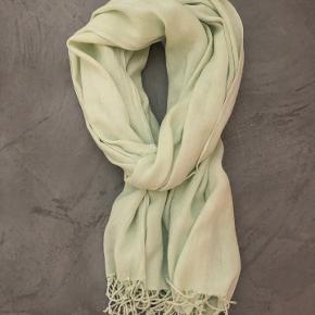 Tørklæde, der giver et flot og farverigt pift til ethvert outfit.  Farven er mintgrøn og tørklæde er i lækkert, blødt stof.   170*70 cm  Fra ikke-ryger og dyrefrit hjem.  Der er to mindre mærker af stræk i stoffet (se billede), men er ikke synligt ved brug.  Sælger ud, da en hel skabshylde er fyldt op med tørklæder uden at blive brugt tilstrækkeligt.