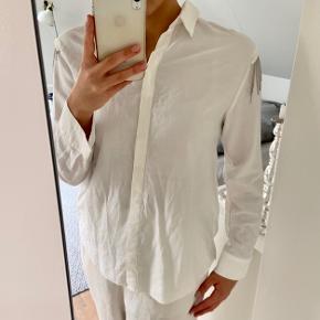 Hvid skjorte fra Zara med små pynte kæder. Skjorten er brugt og har derfor også tegn på slid. Ikke noget stort, men man kan se den er brugt