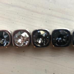 Varetype: Armbånd Størrelse: 18 cm Farve: Sølv  Fint armbånd med similisten i grå røgfarvede sten Sender med dao