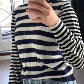 Mørkeblå og hvide striber foran, sorte og hvide striber bagpå, på ærmerne og på kraven.  100% Merino EXTRA FINE