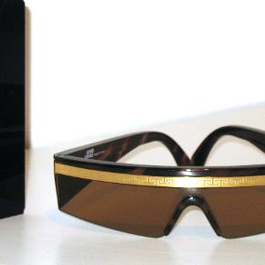 Gianni Versace - Rare Vintage Italian Sunglasses Col. 900 - Gianni Versace Luxury Genuine Vintage Sunglasses. This is an extremely rare pair of Gianni Versace. The sunglasses condition is mint, they haven't been used. It is a collector piece.  Materials: Brown Acetato (Marrone) with golden inserted details in GRECA (Theme Medusa VERSACE)  Lens color: Smoked Brown 100% UV-Protection Made in Italy - Frame measurements: Total frame musk length: 150mm  Temples length: 135mm  Height musk: 35mm  Nose bridge: 15mm