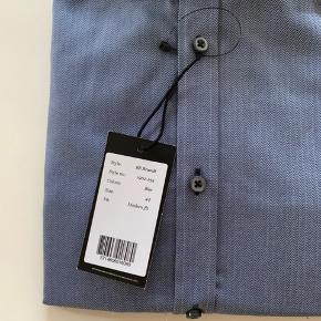 Ny blå skjorte fra Bruun & Stengade str 44. Stadig med mærke.  Køber betaler Porto.